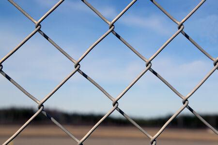 chainlinked: Close-up van een keten verbonden hek met een wazig blauwe hemel landschap op de achtergrond
