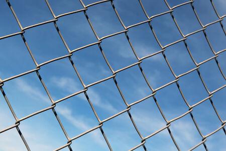 chainlinked: Keten verbonden hek met blauwe hemel als achtergrond.
