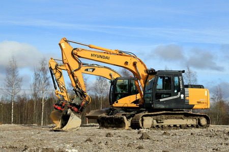 TURKU, FINLAND - APRIL 12, 2014  Cat and Hyundai Robex excavators at construction site  Marketshare Hyundai Heavy Industries Europe increased with more than 30  in 2013
