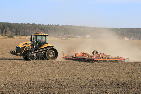 compaction: SALO, FINLAND - APRIL 19, 2014  Farmer cultivating field with Cat Challenge MT765c agricultural crawler tractor and seedbed cultivator  A crawler tractor disperses its weight out over a greater area, which reduces soil compaction