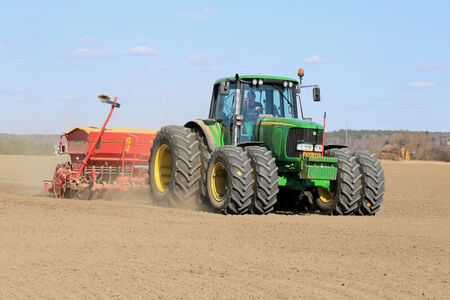 deere: SALO, FINLAND - APRIL 20, 2014  Farmer working the field with John Deere 6620 Agricultural Tractor and Vaderstad Rapid 400C seeder  Finnish farmers are able to hit the fields already in mid-April thanks to unseasonably mild spring  Editorial