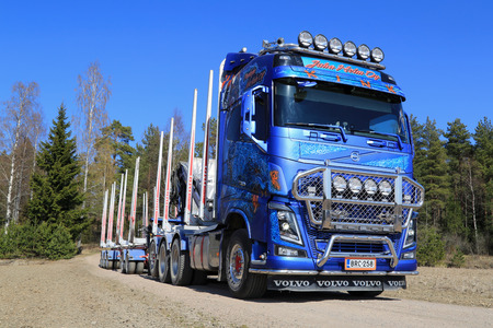 tl: KOSKI TL, FINLAND - APRIL 27, 2014  Customized Volvo FH16 750 timber truck on rural road  The first Euro 6 versions of the Volvo FH16 will be delivered in early June  Editorial