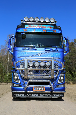 tl: KOSKI TL, FINLAND - APRIL 27, 2014  Customized Volvo FH16 750 timber truck on rural road  With up to 750 hp and 3550 Nm of torque, the new Volvo FH16 retains its position as the strongest truck in the world