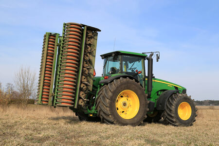 compacting: SALO, FINLAND -  APRIL 19, 2014  John Deere 8430 agricultural tractor with ring roller  The advantages of rolling include breaking up large clumps of soil, compacting the surface, and reduced moisture loss
