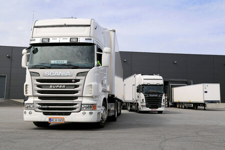tonnes: TURKU, FINLAND - APRIL 26, 2014  White Scania trucks ready to unload at a warehouse  According to Statistics Finland, a total of 71 million tonnes of goods were transported by lorries in the fourth quarter of 2013