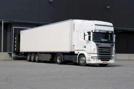 TURKU, FINLAND - APRIL 26, 2014  White Scania R440 truck unloading by a warehouse  According to Statistics Finland, a total of 71 million tonnes of goods were transported by lorries in the fourth quarter of 2013  Redakční