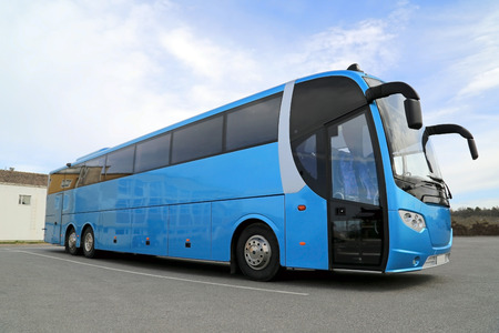 Blue coach bus on parking lot on a clear day at summer. Фото со стока - 28138730