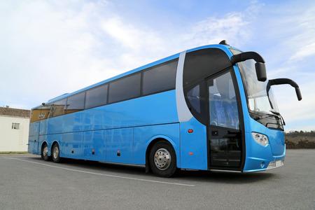 Touring: Niebieski autobus na parkingu w słoneczny dzień w lecie.