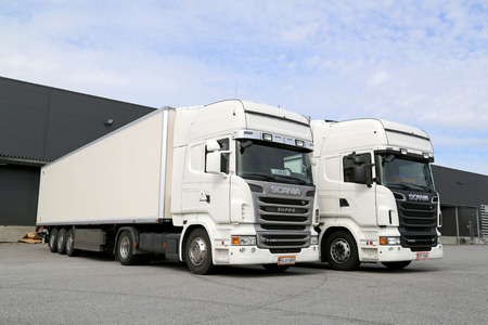 TURKU, FINLAND - APRIL 26, 2014  White Scania R440 and R560 trailer trucks at warehouse  According to Scanias Sustainability Report 2013, Scanias stated goal is to be the leader in sustainable transport solutions