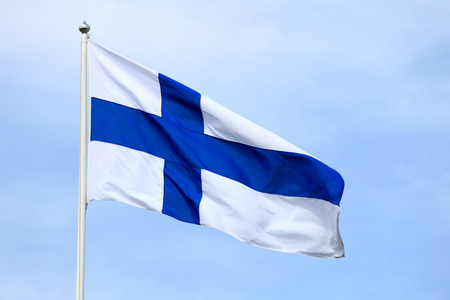 Flag of Finland against pale blue sky.