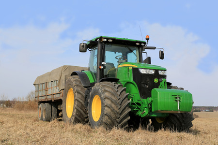 SALO, FINLAND - APRIL 19, 2014: John Deere 7280R Tractor and agricultural trailer by field. Deere Announces Second-Quarter Earnings of $981 Million.
