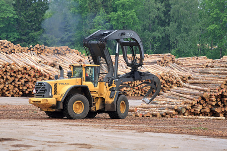 KYRO, FINLAND - JUNE 7, 2014  Volvo L180F High Lift wheel loader working at mill lumber yard   The arm is capable of reaching a lift height of 5,8 m under closed grapple  Stock Photo - 29059524