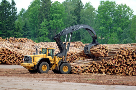 grapple: KYRO, FINLAND - JUNE 7, 2014  Volvo L180F High Lift wheel loader working at mill lumber yard   The L180F HL features a 3 2 m2 grapple, four liquid-filled tires, a log pusher, full cover mudguards with protection bar at the front and a grille guard