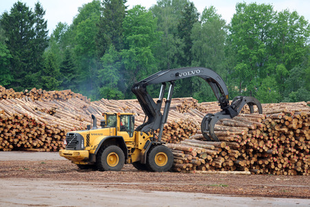 KYRO, FINLAND - JUNE 7, 2014  Volvo L180F High Lift wheel loader working at mill lumber yard   The L180F HL features a 3 2 m2 grapple, four liquid-filled tires, a log pusher, full cover mudguards with protection bar at the front and a grille guard