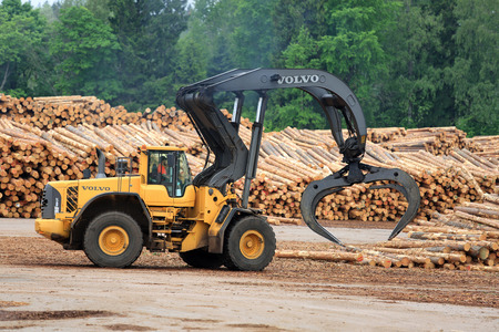 grapple: KYRO, FINLAND - JUNE 7, 2014  Volvo L180F High Lift wheel loader working at mill lumber yard   The L180F HL features a 3,2 m2 grapple, four liquid-filled tires, a log pusher, full cover mudguards with protection bar at the front and a grille guard