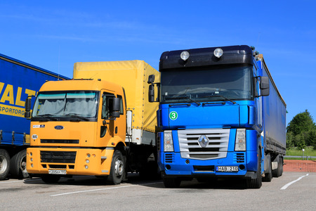magnum: Salo, en Finlande - 15 juin 2014: Yellow Ford Cargo 1830 et bleus camions semi-remorques Renault Magnum gar�s. Ford Cargo a �t� lanc� en 1981, et Renault Magnum a �t� fabriqu� en 1990-2013. �ditoriale