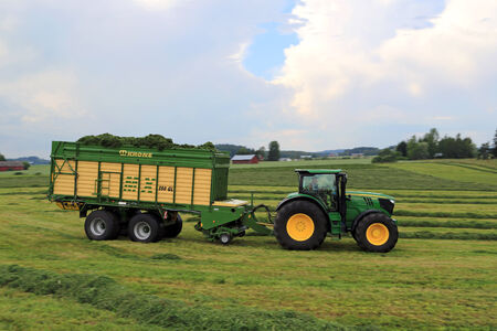 FORSSA, FINLAND - JULY 20, 2014  John Deere 6210R tractor and Krone MX 350 GL forage and discharge wagon collecting silage  Use of wagon instead of trailed forage harvesters offers significant benefits  Background  Motion blur