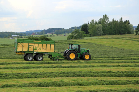 FORSSA, FINLAND - JULY 20, 2014  John Deere 6210R tractor and Krone MX 350 GL forage and discharge wagon collecting silage  Use of wagon instead of trailed forage harvesters offers significant benefits