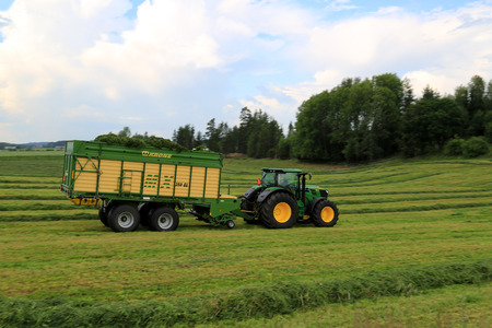 FORSSA, FINLAND - JULY 20, 2014  John Deere 6210R tractor with Krone MX 350 GL forage wagon transports cut hay  Use of wagon offers significant benefits compared to trailed forage harvesters  Background  Motion blur