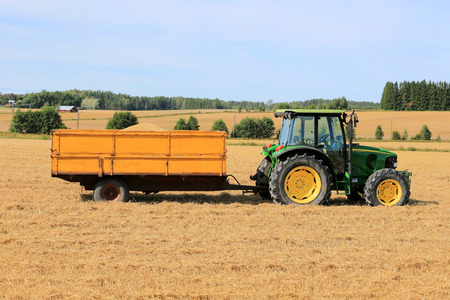 RAASEPORI, FINLAND - AUGUST 17, 2014: John Deere 5820 Agricultural tractor and trailer full of grain on stubble field. John Deere 5820 was manufactured in 2003-2008 in Germany.