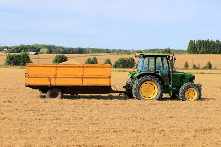 deere: RAASEPORI, FINLAND - AUGUST 17, 2014: John Deere 5820 Agricultural tractor and trailer full of grain on stubble field. John Deere 5820 was manufactured in 2003-2008 in Germany.