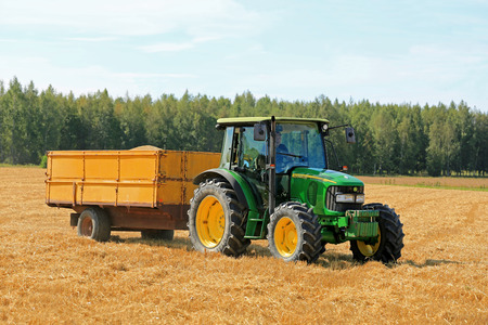 john: RAASEPORI, FINLAND - AUGUST 17, 2014: Unidentified farmer driving a John Deere 5820 Agricultural tractor and trailer full of grain. John Deere 5820 was manufactured in 2003-2008 in Germany.