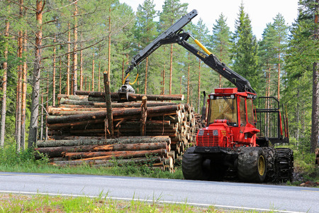 tl: KOSKI TL, FINLAND - AUGUST 16, 2014: Sisu forestry forwarder stacking wood by road. Ca. 95% of Finnish production forests are certified under the Finnish PEFC system. Editorial