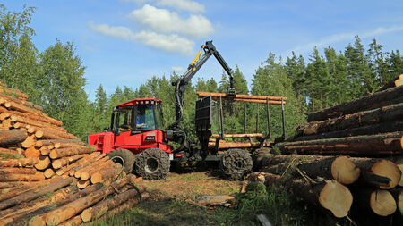 forwarder: RAASEPORI, FINLAND - AUGUST 17, 2014  Unidentified machine operator stacking up wood with Komatsu 830 3 forwarder  Ca  95  of Finnish production forests are certified under the Finnish PEFC system  Editorial