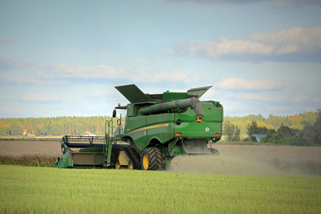ec: SALO, FINLAND - SEPTEMBER 6, 2014: John Deere s670i Combine on field in the evening harvesting Rapeseed. EC estimates the European Rapeseed crop grow by 7% in 2014. Editorial