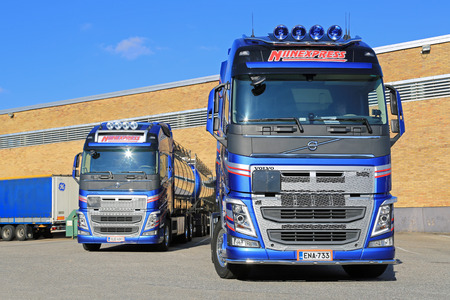 TURKU, FINLAND- SEPTEMBER 13, 2014: Two New Volvo FH chemical tanker trucks by a warehouse. According to Cefic, EU chemicals output is up 1.8 per cent during first 5 months of 2014.
