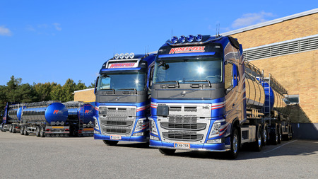 TURKU, FINLAND – SEPTEMBER 13, 2014: Two New Volvo FH chemical tanker trucks by a warehouse. According to Cefic, EU chemicals output is up 1.8 per cent during first 5 months of 2014.