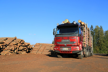 LUVIA, FINLAND - SEPTEMBER 19, 2014: Sisu 18E630 Timber truck at sawmill lumber yard ready to unload. Metla reports 2% growth in Finnish timber trade in Jan-Aug 2014. Photo: Copy space left.