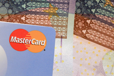 SALO, FINLAND - OCTOBER 19, 2014: MasterCard credit card sign close up over Euro cash. MasterCard Brings Contactless Payment to the 2014 World Series.