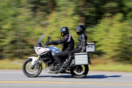 RAASEPORI, FINLAND - SEPTEMBER 7, 2014: Two unidentified bikers ride a motorcycle in high speed.  According to Trafi, there are 238 602 registered motorcycles in Finland in 2014.