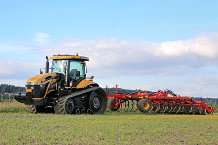 tracked: SALO, FINLAND -SEPTEMBER 6, 2014: Challenger MT765C tracked agricultural tractor and cultivator on field. MT765C has Caterpillar 8.8L 6-cyl diesel engine.