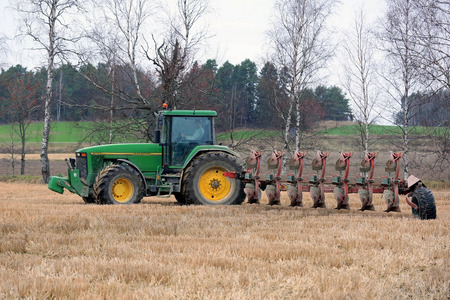 SALO, FINLAND - OCTOBER 25, 2014: Unnamed farmer ploughing a field with John Deere 8100 tractor and Kverneland PB100 plough with 7 furrows. PB100 suits areas and can have up to 8 furrows.