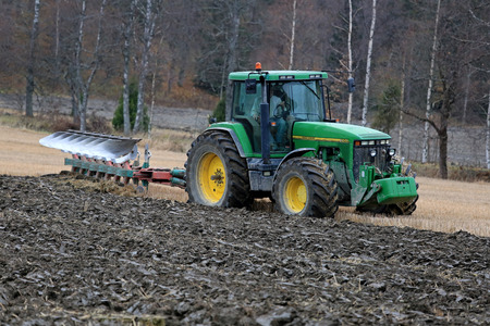 SALO, FINLAND - OCTOBER 25, 2014: Unnamed farmer ploughing a field with John Deere 8100 tractor and Kverneland plough. John Deere 8100 was manufactured between 1995-199 and it has Power Shift Transmission.
