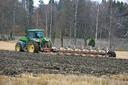 furrows: SALO, FINLAND - OCTOBER 25, 2014: Unnamed farmer ploughing a field with John Deere 8100 tractor and Kverneland PB100 plough with 7 furrows. PB100 is for large areas and can have up to 8 furrows. Editorial