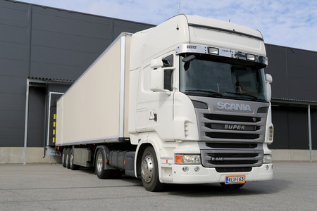 tonnes: TURKU, FINLAND - APRIL 26, 2014: White Scania R440 semi truck unloads at a warehouse. According to Statistic Finland, a total of 67 million tonnes of goods were transported by lorries in the Q2 of 2014.