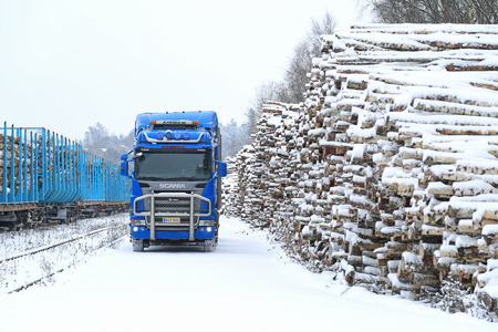 logging railroads: SALO, FINLAND - NOVEMBER 22, 2014: Blue Scania R580 V8 logging truck at Salo railway station. About 25% of Finnish timber is transported to railway stations and loaded onto carriages by trucks.