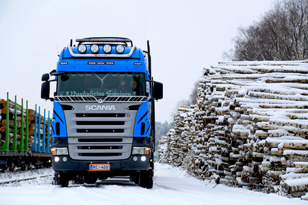 SALO, FINLAND - NOVEMBER 22, 2014: Blue Scania V8 logging truck at Salo railway station. About 25% of Finnish timber is transported to railway stations and loaded onto carriages by trucks.