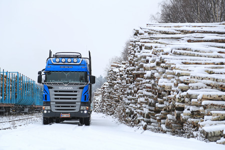 hauling tractor: SALO, FINLAND - NOVEMBER 22, 2014: Blue Scania V8 logging truck at Salo railway station. About 25% of Finnish timber is transported to railway stations and loaded onto carriages by trucks. Editorial