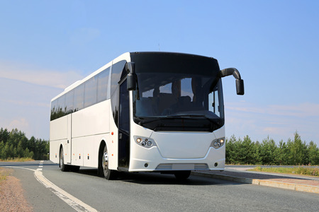 tours: White coach bus on the road at summer. Stock Photo