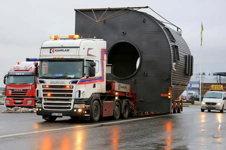 exceeds: FORSSA, FINLAND - NOVEMBER 30, 2014: Scania truck hauls a wide load accompanied by escort cars. On Finnish roads at least one escort vehicle is necessary, if the load exceeds 3,5 m in width.