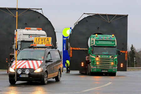 exceeds: FORSSA, FINLAND - NOVEMBER 30, 2014: Pilot car and two trucks with oversize loads. One pilot vehicle with height measuring pole is required, if the load exceeds 5 m in height. Editorial