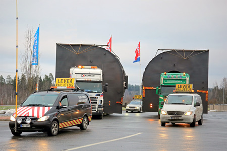 exceeds: FORSSA, FINLAND - NOVEMBER 30, 2014: Pilot cars and two trucks with oversize loads about to continue their journey. One pilot vehicle with height measuring pole is required, if the load exceeds 5 m in height.