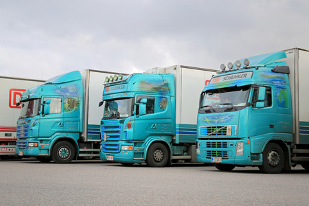 tonnes: NAANTALI, FINLAND - OCTOBER 11, 2014: Fleet of three colorful trailer trucks on a yard. According to Statistic Finland, a total of 67 million tonnes of goods were transported by lorries in the second quarter of 2014.