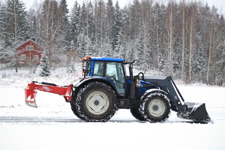 SALO, FINLAND – NOVEMBER 22, 2014: Valtra tractor removes snow with bucket and VM  road drag.  In Finland, snow removal expenses can be considerable.