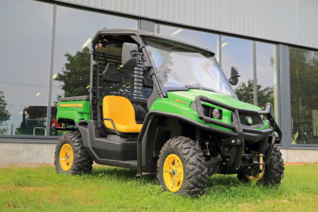 deere: SALO, FINLAND - AUGUST 9, 2014: John Deere Gator XUV550 Crossover Utility Vehicle on grass. The Gator has a V-twin engine and independent four-wheel suspension.