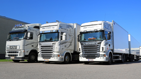 tonnes: TURKU, FINLAND - SEPTEMBER 13, 2014: Fleet of white Scania R series and Volvo FH trucks by a warehouse. According to Statistic Finland, a total of 67 million tonnes of goods were transported by lorries in Q2 of 2014. Editorial